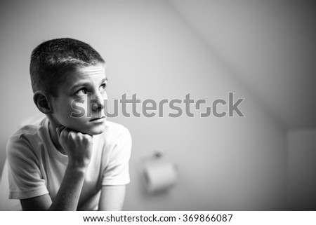 Close up Contemplative Young Handsome Boy Sitting on the Toilet Inside the House and Looking up with Face Leaning on his Hand in Monochrome Color. - stock photo