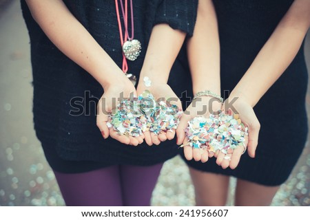 close up couple girls hands with confetti carnival outdoor - stock photo