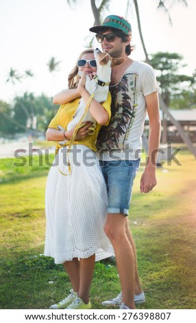 Close-up couple in love playing on the beach in summer sunny evening,with dog. summer beach portrait of young couple in love,wear sunglasses,cap, yellow shirt, island romance.Summer store - stock photo