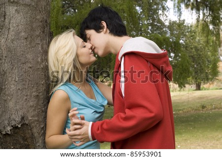 Close up Couple kissing next to tree in garden or park - stock photo