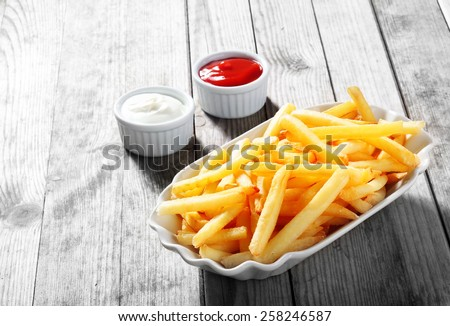 Close up Crispy Potato Fries on White Plate with Two Dipping Sauce, Served on Rustic Wooden Table - stock photo