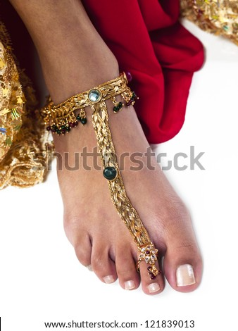 Close-up cropped image of a woman wearing gold ankle bracelet over white background. - stock photo