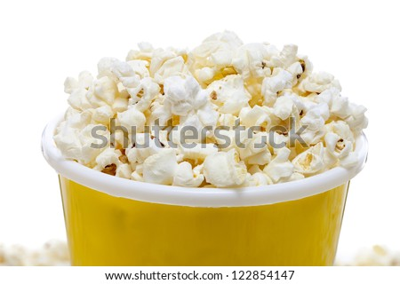 Close-up cropped image of yellow tumbler full of salted popcorn - stock photo