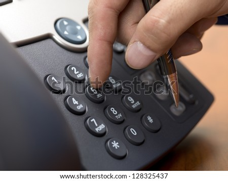 Close-up cropped shot of human hand dialing from a modern land line phone. - stock photo
