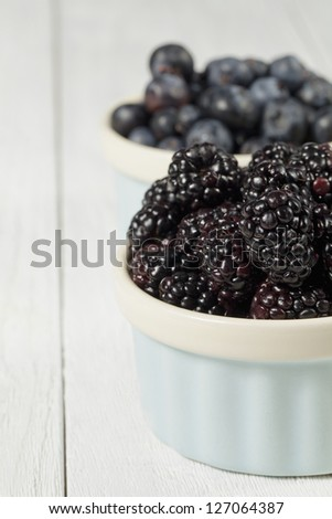 Close-up cropped shot of red grapes and blackberries in bowl. - stock photo