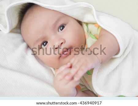 Close-up Cute Asian male baby with a towel. 3 months baby boy lying on a towel. Blurred background. - stock photo