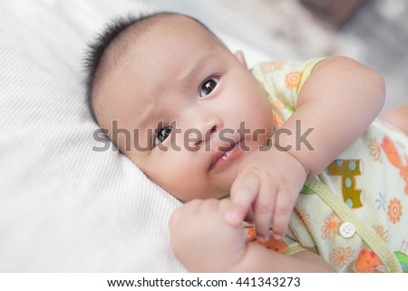 Close-up Cute Asian male baby with a towel. 3 months baby boy lying on a towel. Healthy baby boy. Blurred background. - stock photo