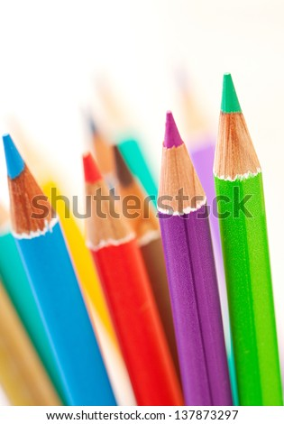 Close up detail of a bunch of colored school art pencils pointing upwards, isolated on a plain background. - stock photo