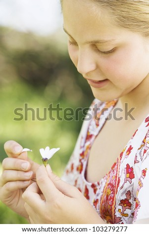 Close up detail of a girl's hands pulling the last petals off a daisy flower. - stock photo