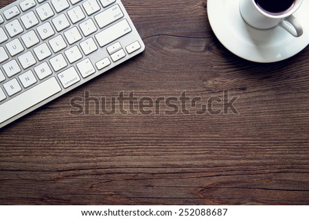 Close up detail of an aluminum keyboard on a vintage wooden desk. Technology, finance, business, baking, online shopping and education concept. Natural window light. - stock photo