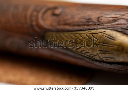 Close up detail of an engraved pattern on an old wooden pistol. - stock photo