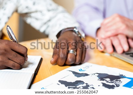 Close up detail of black business man signing documents with caucasian colleague in background. - stock photo