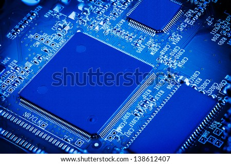 Close up detail of blue microchip circuit board. - stock photo