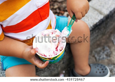 Close-up detail of child eating ice cream. Outdoor at the cafe - stock photo