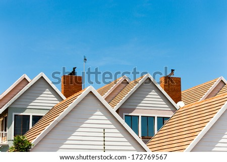 Close up detail of complex house rooftops against blue sky. - stock photo