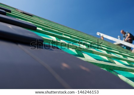 Close-up detail of gray slate tiles on an unfinished roof with wooden beams on the background - stock photo