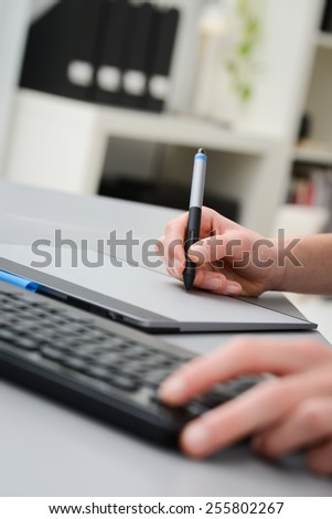 close up detail of hands working with graphic tablet and a desktop keyboard - stock photo