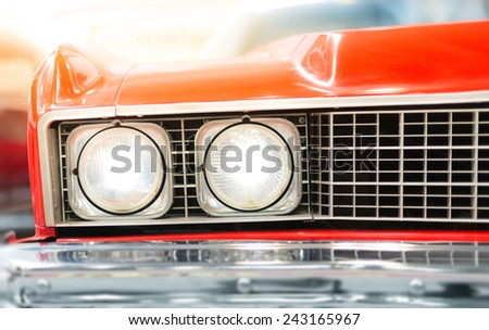 Close Up Detail of Headlight of Shiny Red Classic Car - stock photo