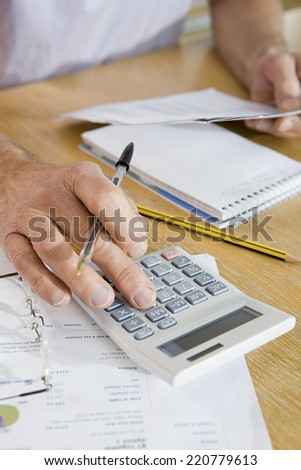 Close-up detail of older man's hand holding a pen and using a calculator with paperwork in background - stock photo