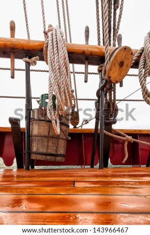 Close up detail of ropes, rigging, wooden bucket, pulley and the wood deck of a classic tall ship schooner at sea. - stock photo