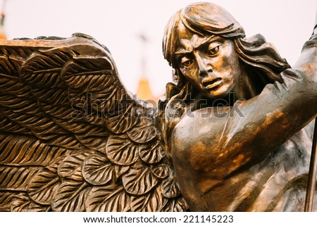 Close Up Detail Of Statue Of Archangel Michael With Outstretched Wings, Thrusting Spear Into Dragon Before Red Catholic Church Of St. Simon And St. Helena On Independence Square In Minsk, Belarus - stock photo