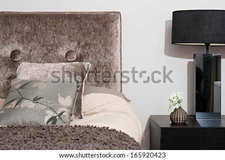 Close up detail view of a bed head in an elegant hotel bedroom with a lamp and side table, cushions and pillows. Home interior with no people. - stock photo