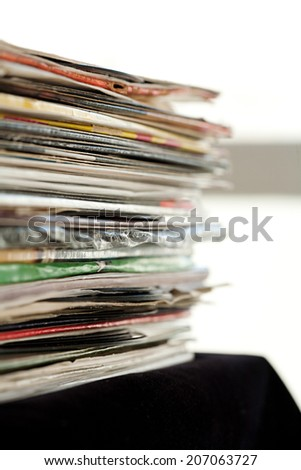 Close up detail view of a pile of old and used vinyl records and albums stacked up in a night club interior. Music and sound interests collection. - stock photo