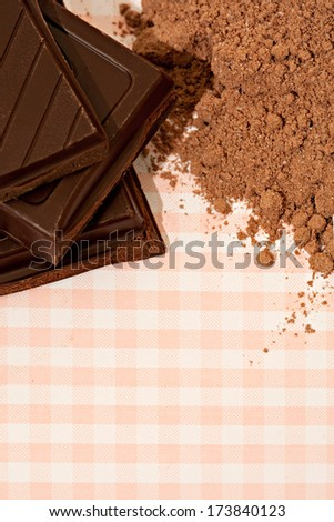 Close up detail view of a small pile of organic dark chocolate squares bars and cocoa powder on a kitchen table with checked table cloth. Desert cooking sweet food ingredients. - stock photo