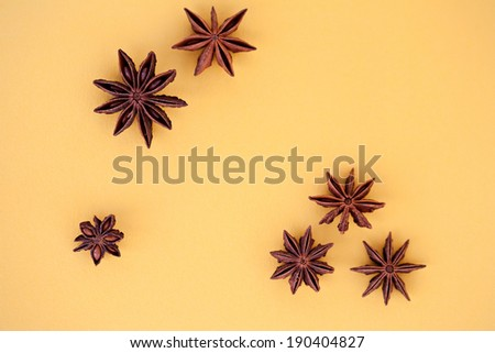 Close up detail view of a star shaped natural aniseed raw spice on a yellow table in a home cooking kitchen. Aromatic and flavorful condiments and ingredients. - stock photo