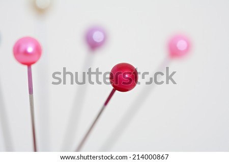 Close up detail view of a variety of sewing pins and needles standing against a white background in a dressmaking fashion interior. Still life of shining sewing pins heads. - stock photo