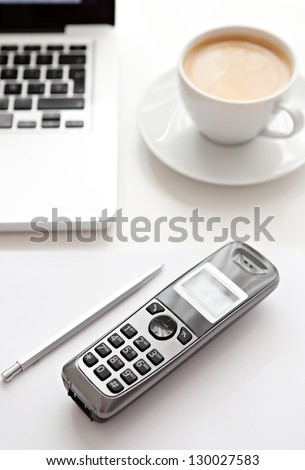 Close up detail view of a white work desk with a laptop computer, a telephone and a cup of coffee, interior. - stock photo