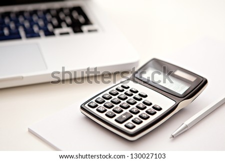 Close up detail view of a white work desk with a laptop computer and a calculator with numbers on the screen. - stock photo
