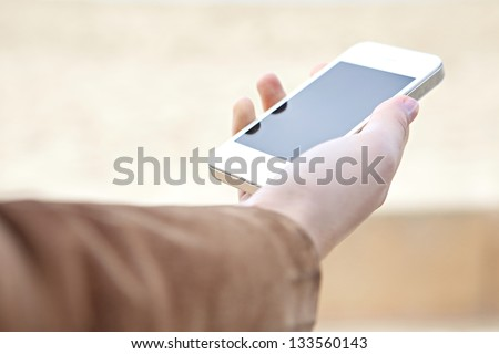 Close up detail view of a woman's hand holding a modern smart phone with a blank screen against a neutral background. - stock photo