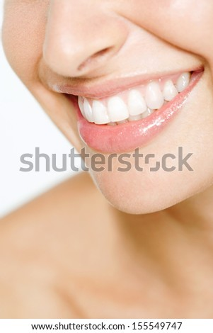 Close up detail view of a young attractive woman half face with a clean white teeth smiling and being expressive wearing soft pink lipstick gloss. - stock photo