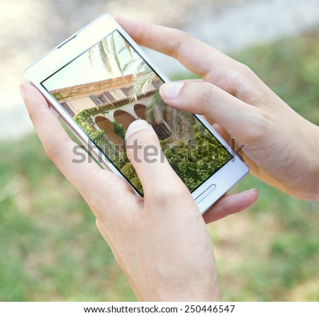 Close up detail view of a young tourist woman hands holding and using a touch screen smartphone mobile device, flicking through holiday pictures on vacation. Travel and lifestyle technology. - stock photo