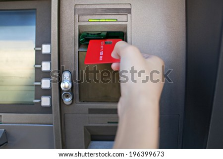 Close up detail view of a young woman hand holding and inserting a red credit card in a cash point machine with a reflective screen, outdoors. Finances and money availability funds. - stock photo
