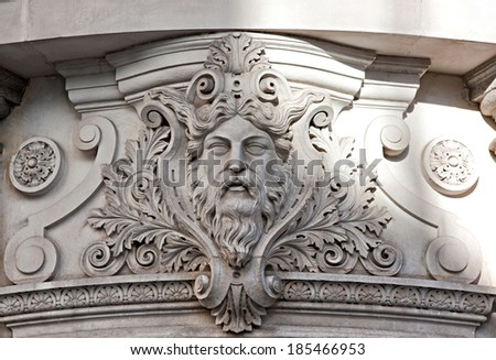 Close up detail view of an old stone building front exterior in the city of London with decorative carvings and artistic sculptures on a sunny day. Craftsmanship in classic centenary architecture. - stock photo