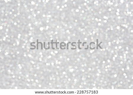Close up detail view of silver glitter background shining and reflecting light with stars in a soft blurred view. Glitter texture. Party, celebration, abstract and festive background textures. - stock photo