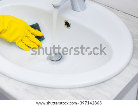 Close up detail view on hand covered with yellow rubber glove wiping down sink bowl with blue sponge and running water - stock photo