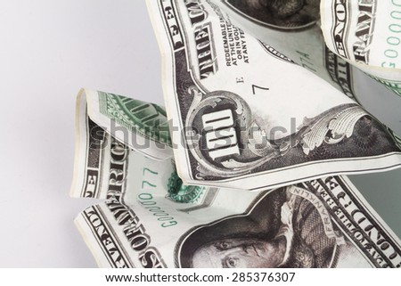 Close up detailed top view of crumpled one hundred dollar banknotes, isolated on white background. - stock photo