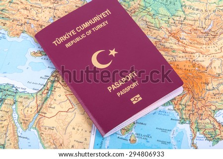 Close up detailed view of a Turkish passport lying on a world map, with Republic of Turkey and Passport text in turkish. - stock photo