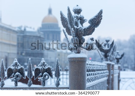 Close up details fence decorations with the Russian imperial double-headed eagle symbol covered with snow on Palace Square, St. Petersburg, Russia - stock photo