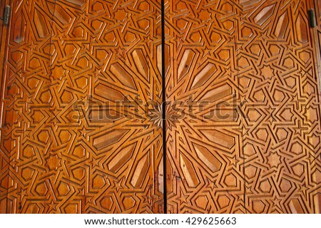 Close-up details of an ornate door of carved cedar at the Bou Inania madrasa in the Fes el Bali medina in Fez, Morocco - stock photo