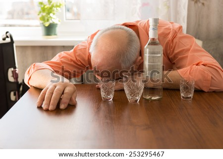Close up Drunk Bald Elderly Taking a Nap on the Wooden Table with Vodka and Small Glasses. - stock photo