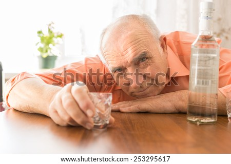 Close up Drunk Elderly Holding Small Shot Glass at the Wooden Table with Vodka While Looking at the Camera. - stock photo
