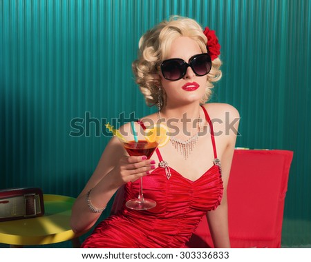 Close up Elegant Blond Young Woman Wearing Sexy Red Fashion with Sunglasses, Holding a Martini Drink - stock photo
