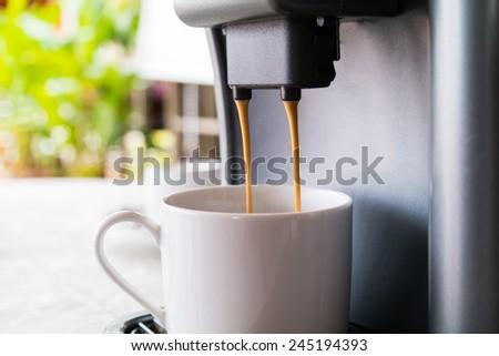 Close up espresso preparing in white ceramic cup from automatic coffee maker machine - stock photo