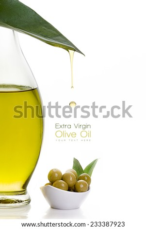 Close up extra olive oil on glass bottle with olive seeds on white bowl and a fresh green leaf with a droplet suspended midair over a white background with copy space. Template design with sample text - stock photo
