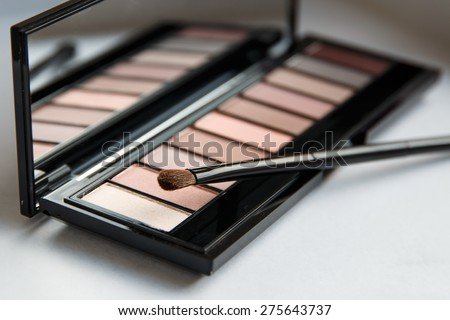 Close Up Eyeshadow Brush on Palette of Rose Nude Colors Eyeshadow. Professional make-up. Pastel Colours. - stock photo