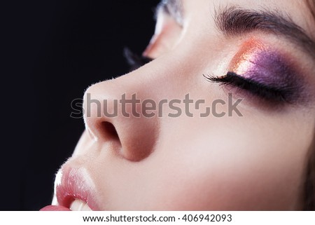 Close-up face, bright eye shadow, makeup. Shallow depth of field, black background - stock photo